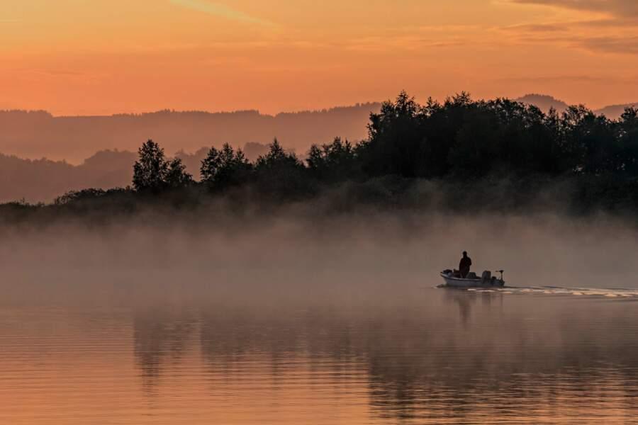 Pêcheur au petit jour sur le lac de Wallersee, au nord-ouest de l'Autriche
