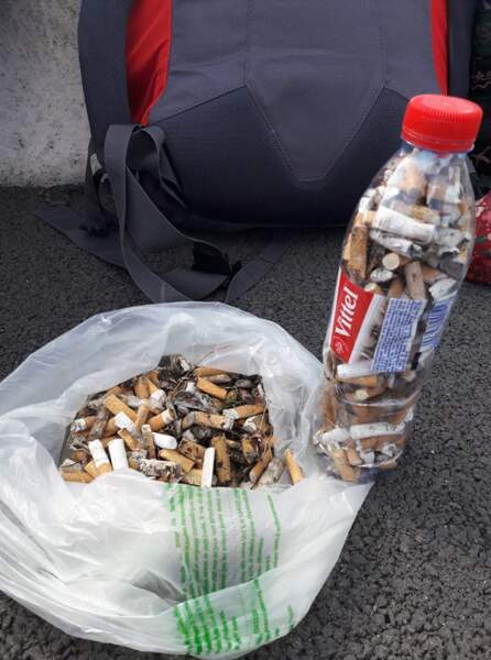Remplir une bouteille de mégots de cigarette trouvés sur le bord de la route