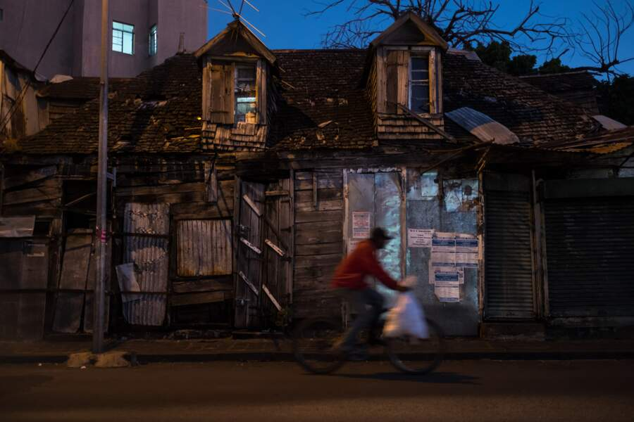 Un cycliste passe devant une vieille maison créole de Port Louis, la capitale