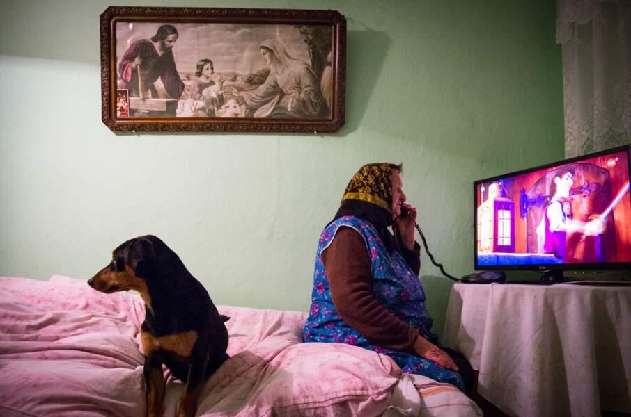 Une grand-mère et son chien devant la télé à Grochowice, en Pologne