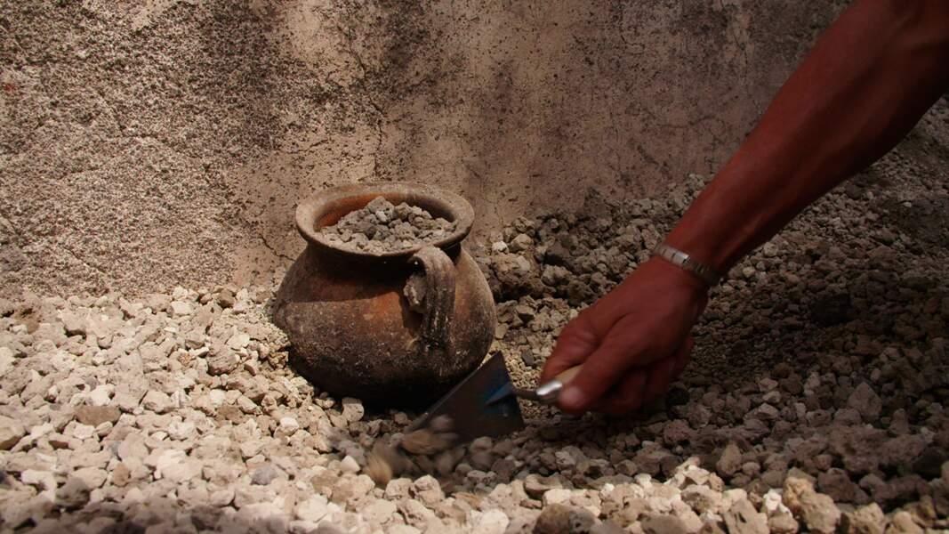 Un récipient pour la cuisson des aliments émerge du lapilli lors de l'excavation