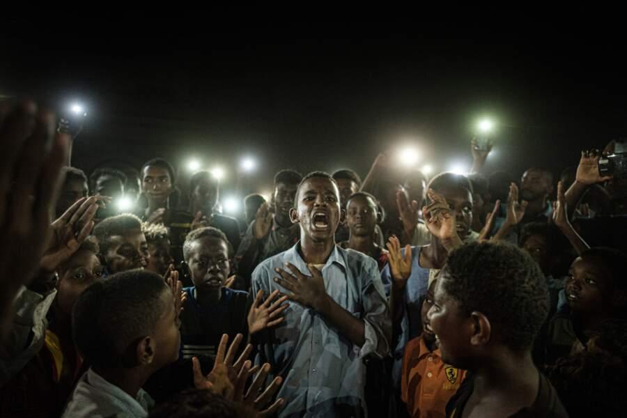 Un jeune homme récite un poème au milieu d'un groupe de manifestants. Khartoum, Soudan, 19 juin 2019