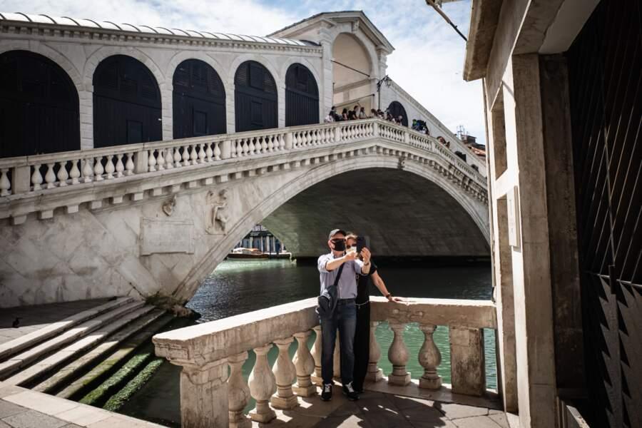 Des touristes italiens se photographiant devant le pont du Rialto