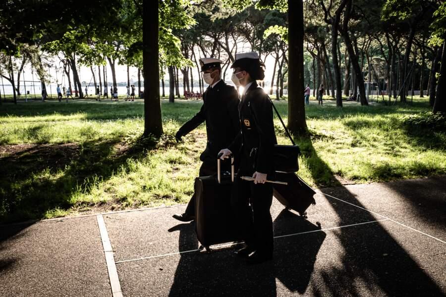Officiers de marine marchant avec leurs valises à Sant'Elena