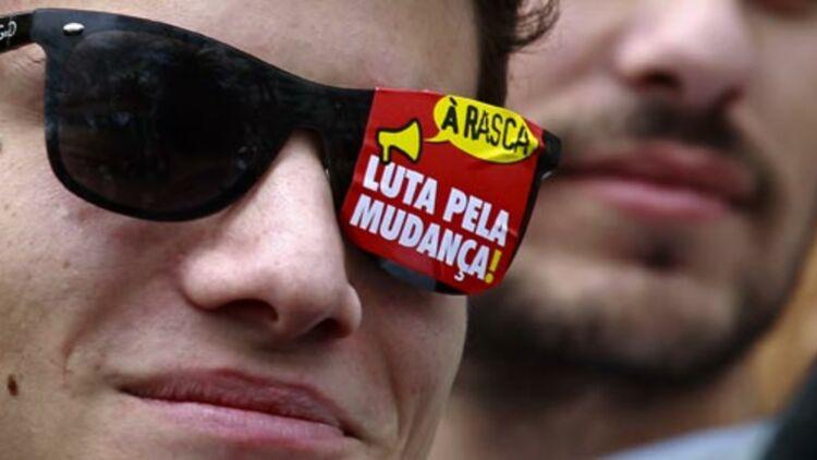 """Un jeune du mouvement """"Geraçao à rasca"""" (""""Génération dans la dèche"""") manifeste le 12 mars 2011 à Lisbonne. Sur ses lunettes, """"Lutte pour le changement !"""". © REUTERS."""