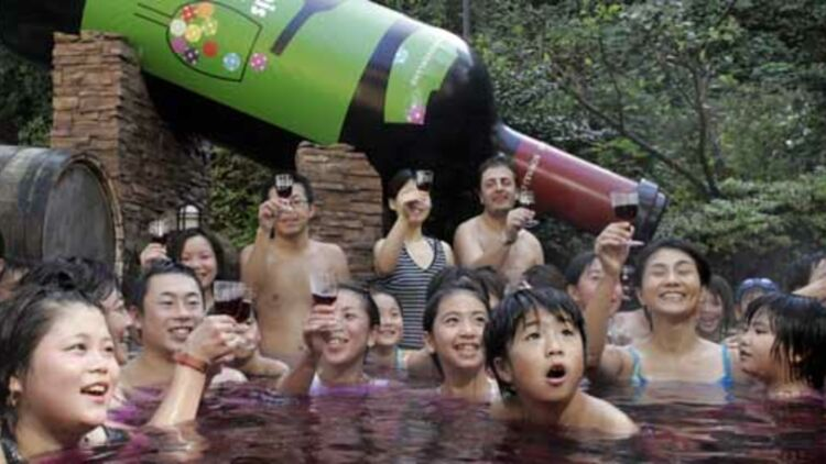 Des Japonais dégustent un verre dans un bain de Beaujolais nouveau, près de la ville de Hakone. © REUTERS.