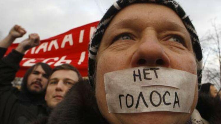 """Des citoyens russes manifestent à Saint-Petersbourg, le 10 décembre 2011. Sur l'autocollant, """"pas de voix"""". © REUTERS."""