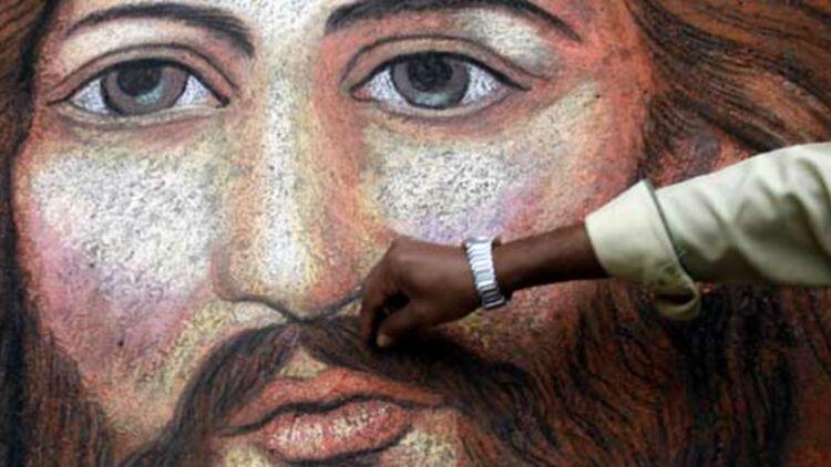 Un peintre de rue indien apporte les touches finales à son portrait de Jésus, à Calcutta. Crédits : REUTERS.