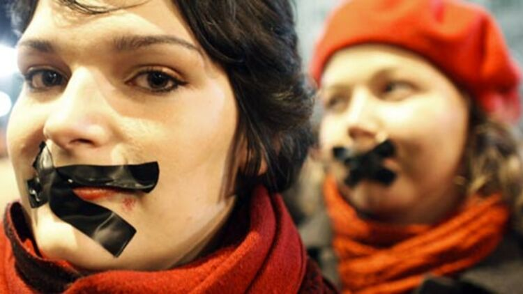 Des Hongrois, la bouche baillonnée, lors d'une manifestation contre une loi sur les médias, devant le Parlement à Budapest, 14 janvier 2011 © REUTERS