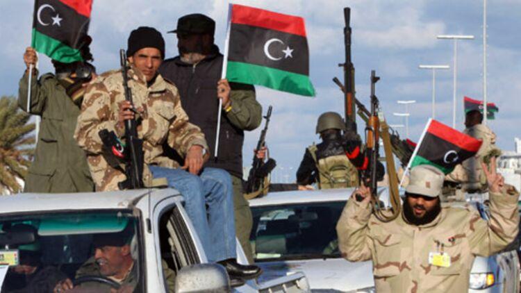 Mardi 14 février, des membres du Conseil National de Transition, actuellement au pouvoir en Libye, paradent dans les rues de la capitale. © REUTERS.