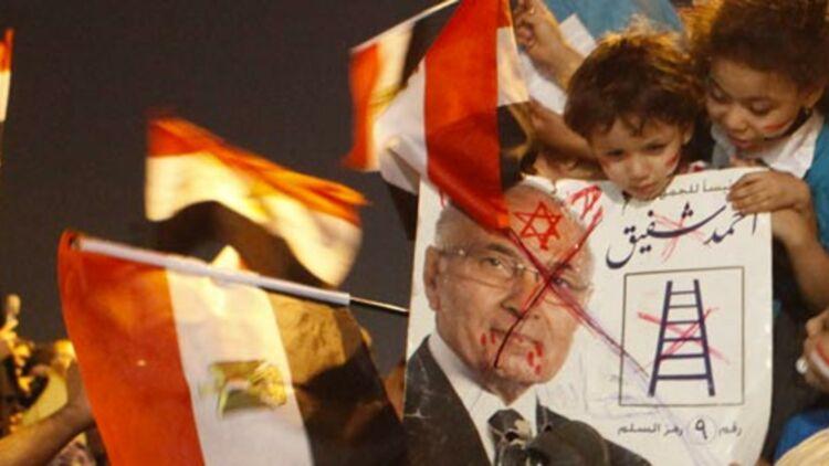 Des supporters de Mohammed Morsi, candidat des Frères musulmans à la présidentielle, portent un poster tagué de son rival Ahmed Chafiq, au Caire, le 18 juin 2012. © REUTERS