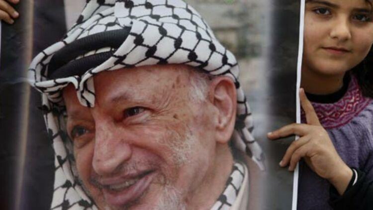 Une fillette palestinienne montre un poster du leader palestinien Yasser Arafat, le 1er janvier 2011. Un documentaire d'Al-Jazeera soutient la thèse que l'ex-leader de l'OLP serait mort empoisonné au polonium. © 2004