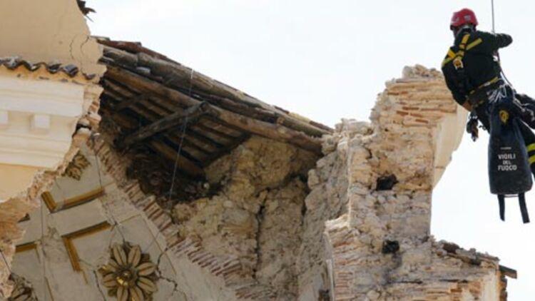 Un pompier inspecte une église endommagée par le séisme dans le centre de L'Aquila, le 8 avril 2009. © REUTERS