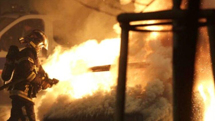 Un pompier asperge d'eau une voiture en feu dans un quartier de Neuhof (Strasbourg), dans la nuit du 31 décembre 2012. © REUTERS