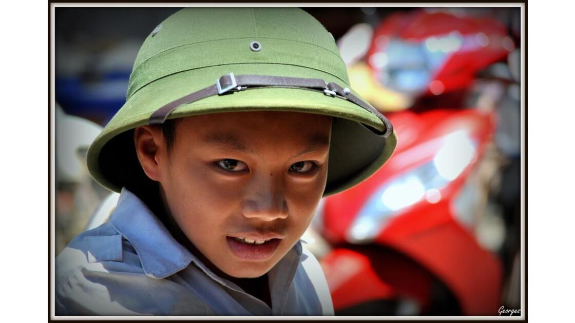 Enfant des rues portant casque colonial