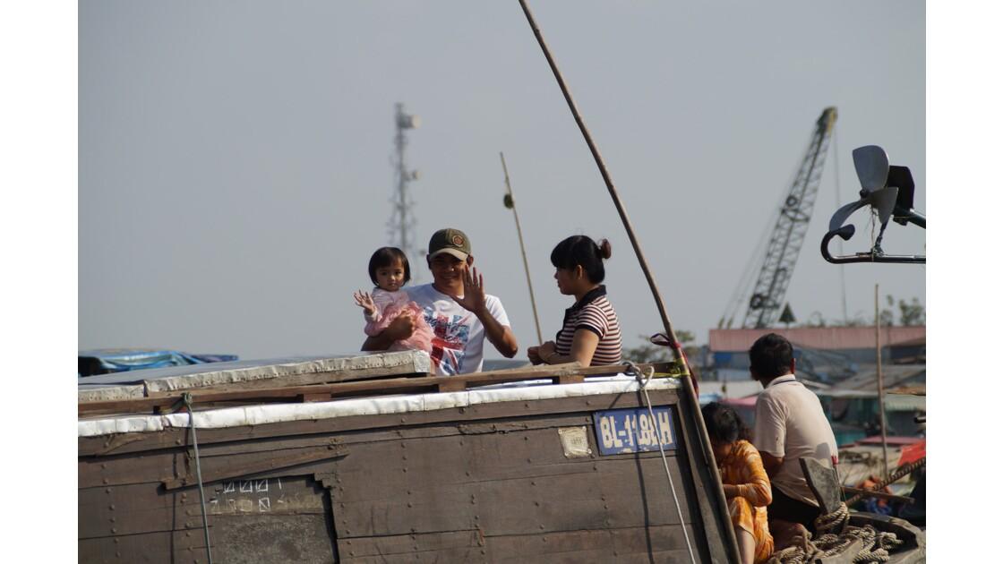 Famille vietnamienne sur un bateau marchand de Cai Rang