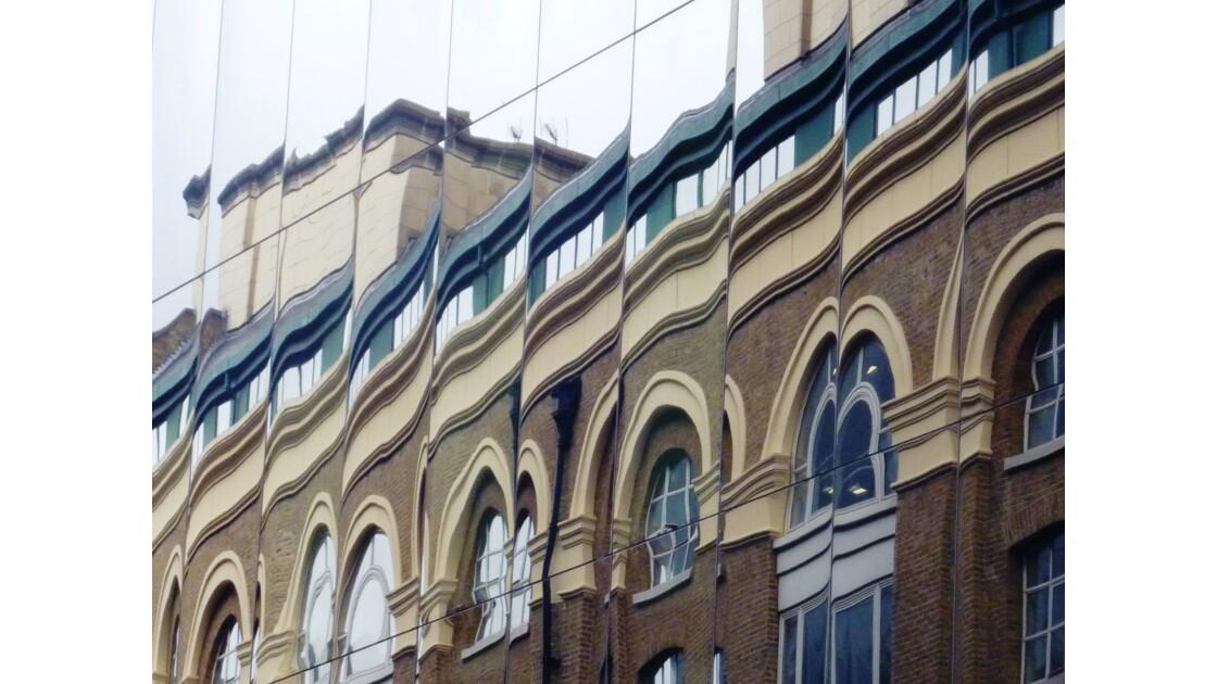 Londres - Jeu de reflets d'un bâtiment classique sur la façade d'un immeuble moderne