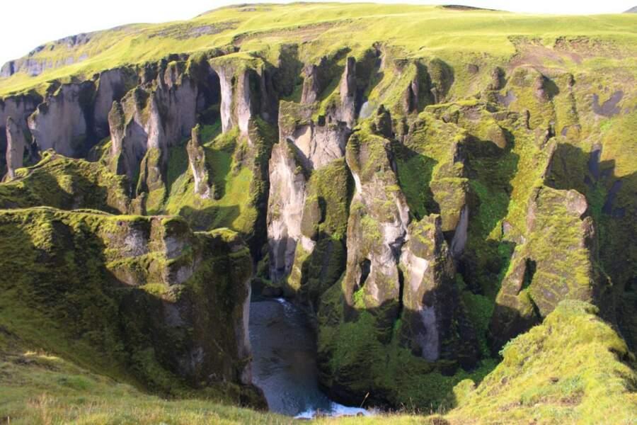 Chute d'eau jaillissant des rochers verts de mousse, en Islande