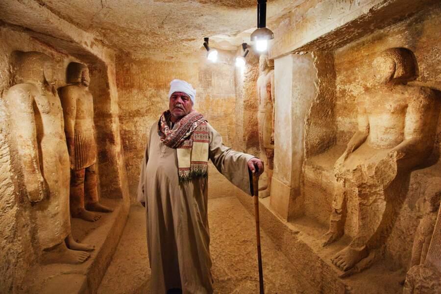 Un gardien prend la pose devant des statues dans une mastaba de la nécropole de Fraser