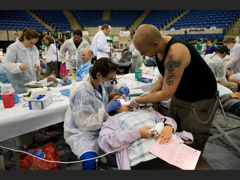 Un homme donne un coup de main à la dentiste qui soigne sa mère (université de Lincoln, Harrogate, Tennessee, Etats-Unis).