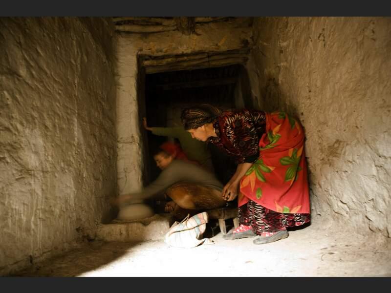 Fatima et sa fille Soumia, autour de la meule à graines, à Tilfitine, dans le Haut-Atlas (Maroc).