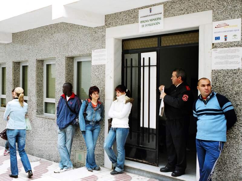 Le matin les candidats à l'immigration font la queue devant l'entrée du bâtiment.