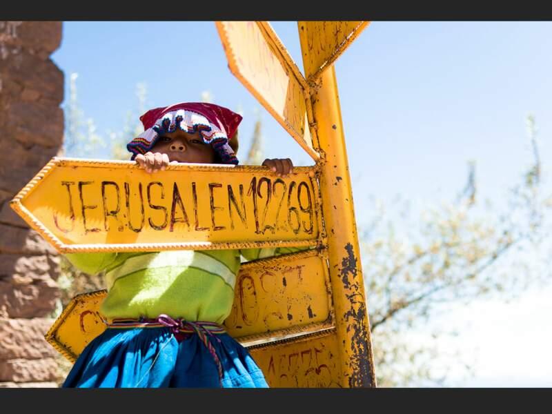 La même petite fille joue avec un panneau indiquant la direction de Jérusalem, sur l'île de Taquile, sur le lac Titicaca (Pérou).