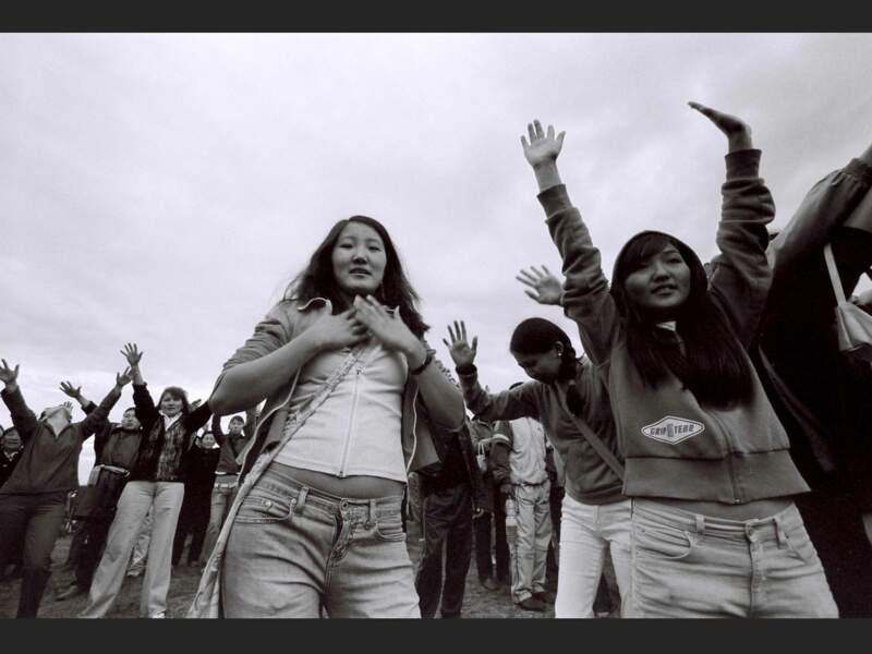 Des jeunes gens se rassemblent, mains tendues vers le ciel, en attendant le soleil (Sibérie, Russie).