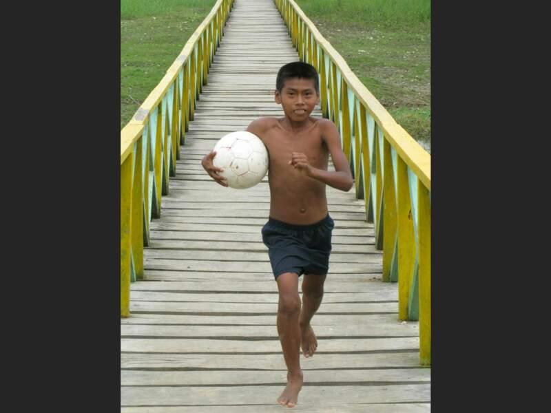 Un enfant colombien court avec son ballon à Leticia, en Colombie.
