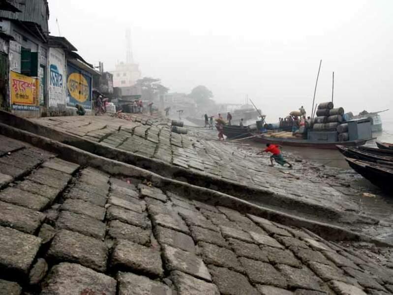 Des hommes s'affairent à charger et décharger de la marchandise sur les quais du fleuve Rupsha, à Khulna, au Bangladesh.