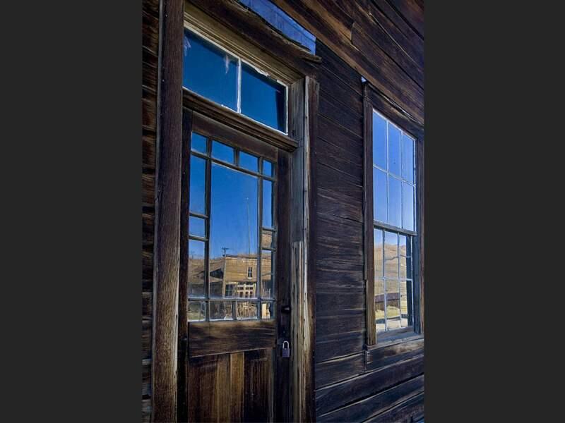 Les mines abandonnées de Bodie se reflètent dans les vitres d'une vieille bâtisse (Californie, Etats-Unis).