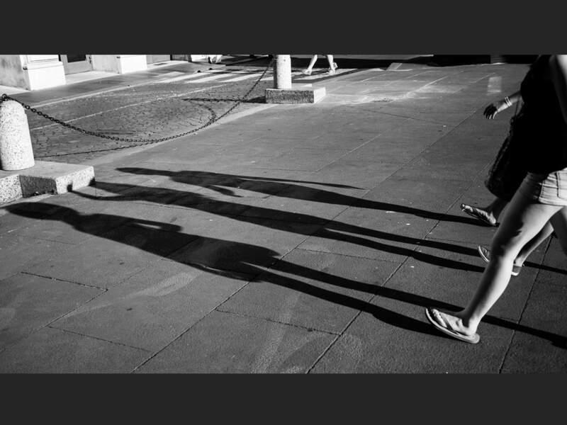 Les ombres de trois promeneuses se dessinent sur la place du Parlement italien, à Rome, en Italie.