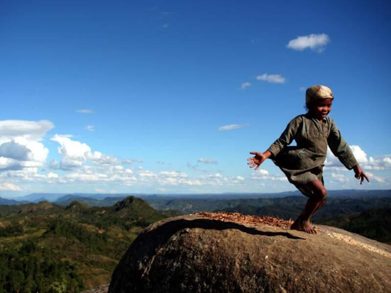 Une petite fille s'amuse sur un rocher, à l'entrée du village d'Antoetra.