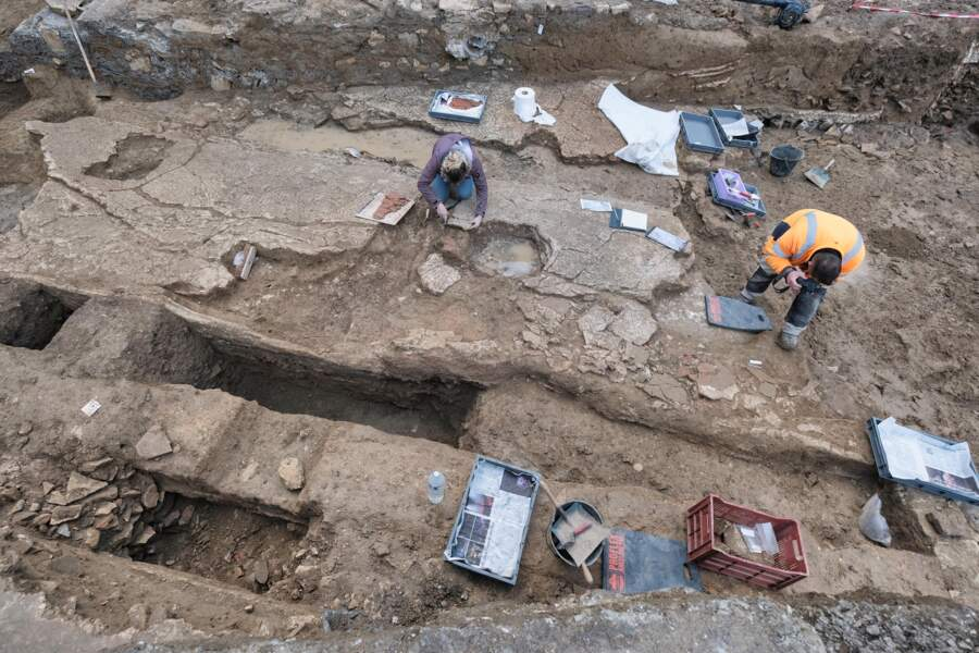 Dépose des enduits peints de deux parois opposées découverts effondrés sur le sol d'une pièce de  réception d'une domus.
