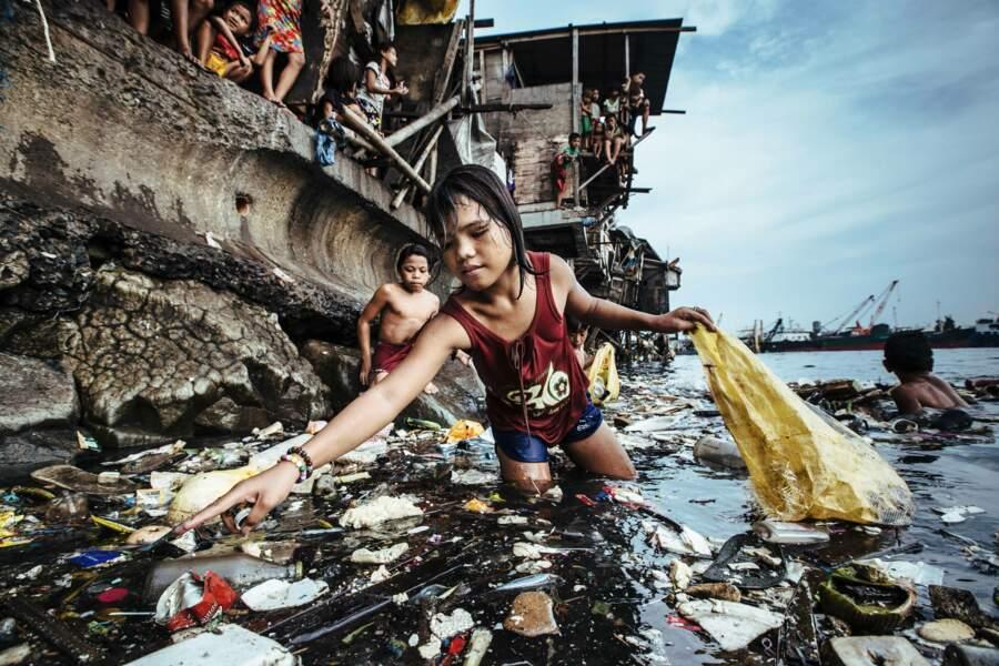 Une fillette ramasse les déchets plastique dans les eaux marines de Manille, aux Philippines, en 2019