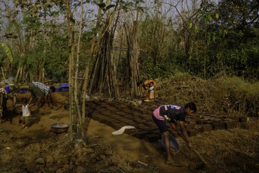 Fabrication de briques en terre séchée pour les maisons des Warli